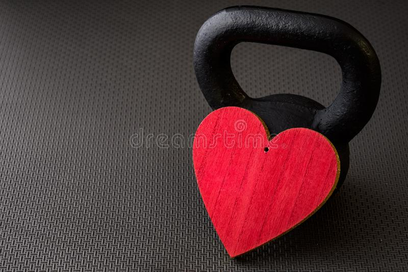 Black kettlebell on a black gym floor with large red heart. To celebrate Valentine's Day fitness royalty free stock photography