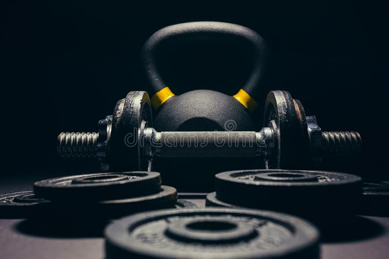 Black kettlebell  with yellow marking with free weights and plates royalty free stock image