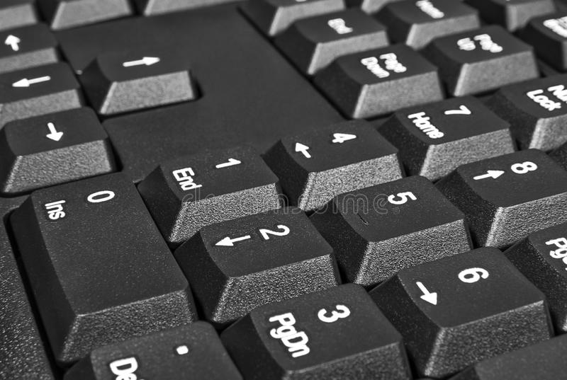 Black keyboard with numbers and arrows on the buttons. Closeup stock photography