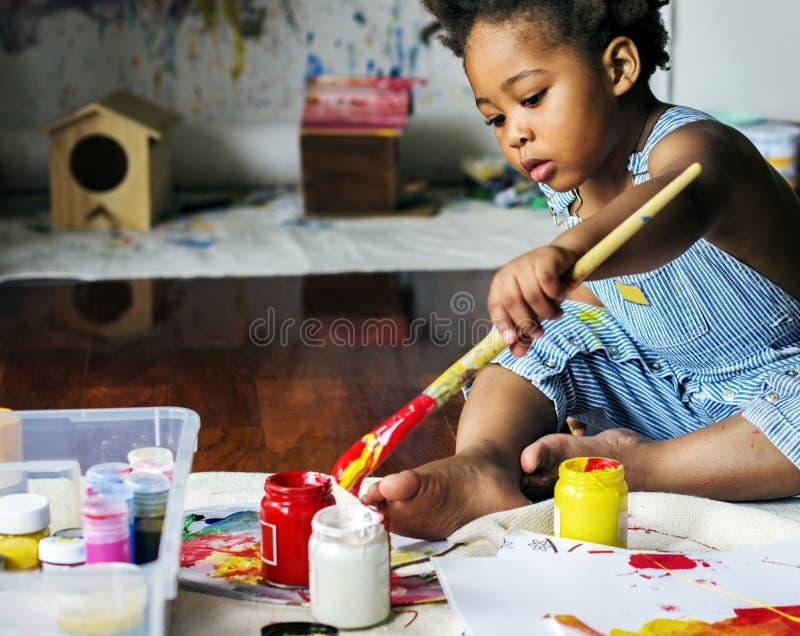 Black kid enjoying his painting royalty free stock photography