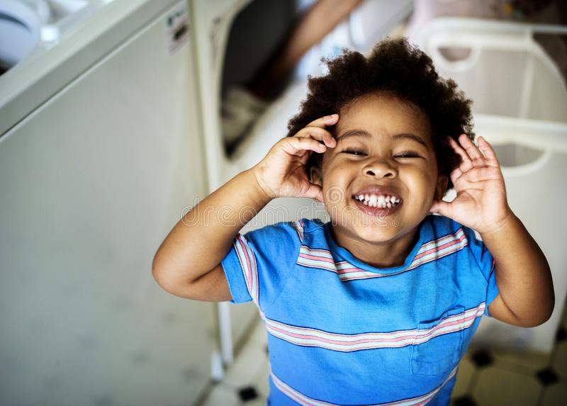 Black kid smiling in the laundry room stock image