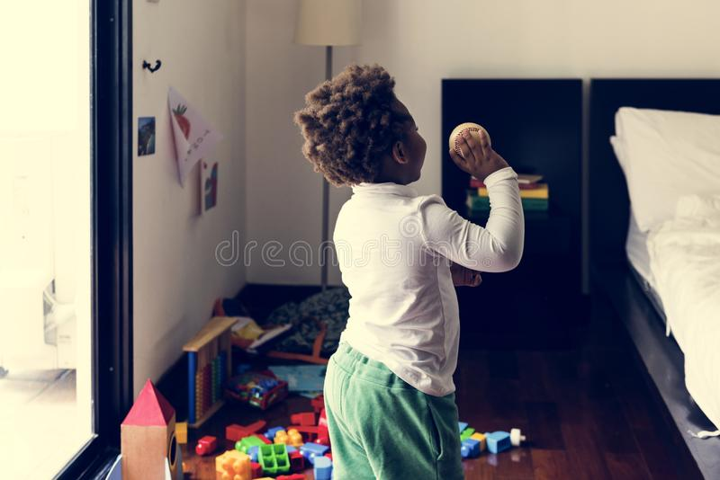 Black kid throwing baseball ball in the room stock photo