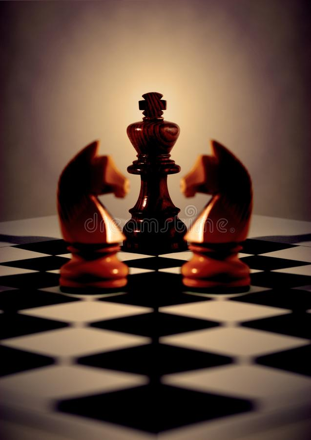 Chess Black King and Two White Knights. Black king with light behind, two white knights mirrored for symmetry, on diagonal chess board. Concepts business or stock images