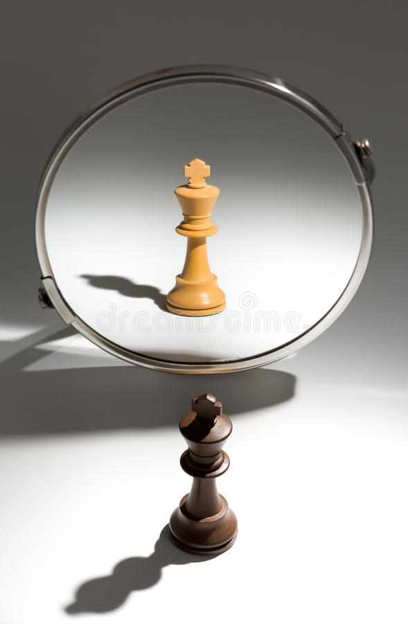 A black king is looking in a mirror to see himself as a white king. royalty free stock images