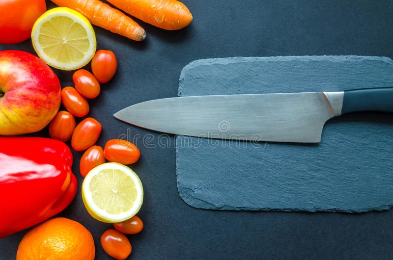 Black Kitchen Knife With Fruits and Vegetable on Table stock images