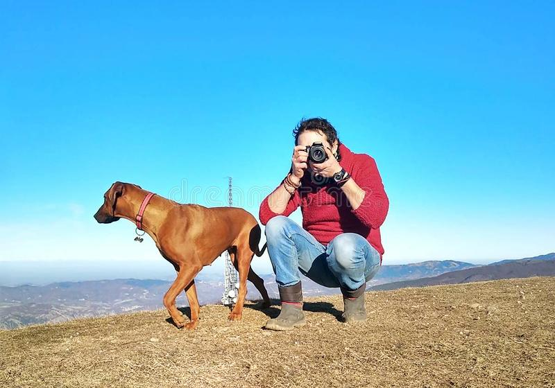 A Rhodesian Ridgeback with his owner, while he's taking a photo with a reflex. On the background you can see the mountains. With a bit of dusk, altitude royalty free stock images