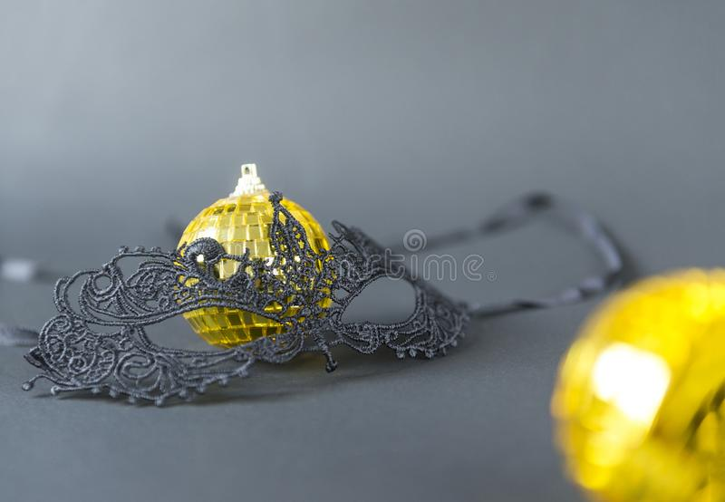 Black, lace masquerade mask, gold Christmas balls on a black background, Christmas decor. 1 black lace masquerade mask, 2 gold Christmas balls on a black stock image