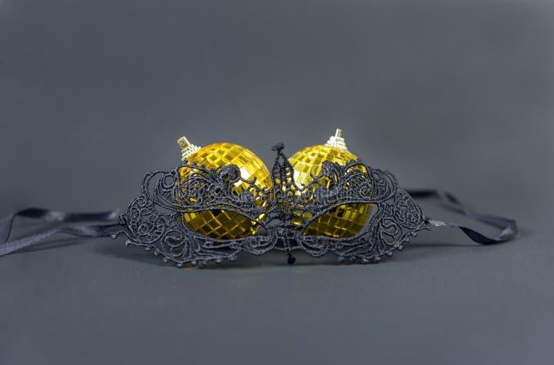 Black lace masquerade mask, Golden Christmas balls on a black ba. 1 black lace masquerade mask, Golden Christmas balls on a black background, Christmas decor stock image