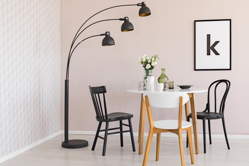 Black lamp above chairs and wooden table with flowers in dining room interior with poster. Real photo vector illustration