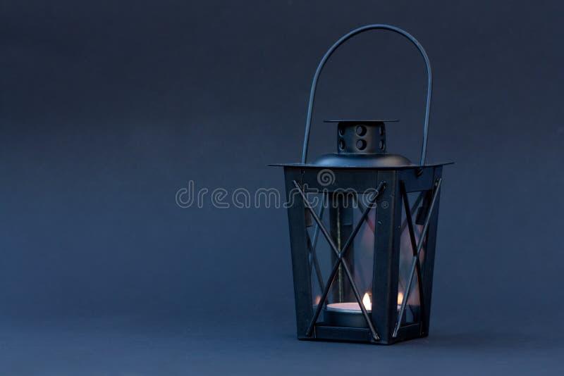 Black lantern on blue background. Black lantern with burning candle on dark blue background stock image