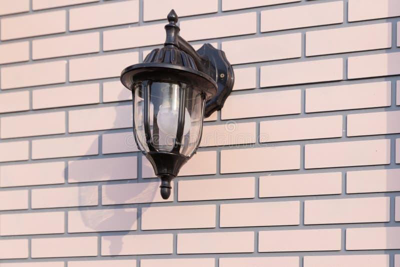 Black Lantern on brick wall. With shadow royalty free stock photos
