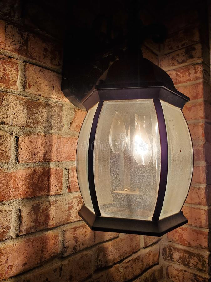 Black Lantern on Brick Wall. Light, glow, vintage, rustic royalty free stock photo