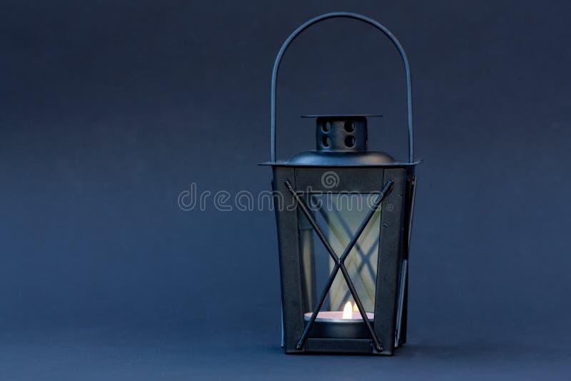 Black lantern on blue background. Black lantern with burning candle on dark blue background stock photos