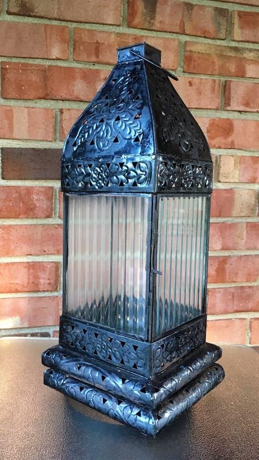 Black lantern. Black metallic lantern against brick wall royalty free stock photos