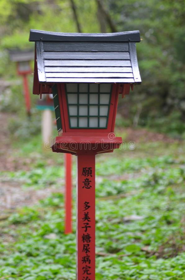 A red and black lantern with Japanese lettering in a park. A black lantern with a red pole is in a park. Japanese lettering in black is on the pole. Other lamps royalty free stock images