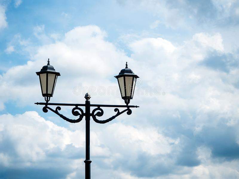 Black lantern in retro style against. The sky with clouds stock photography