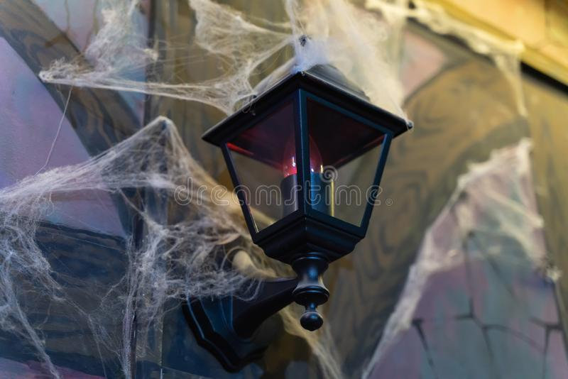 Black lantern in retro style shrouded in cobwebs on the wall. As a background royalty free stock photography