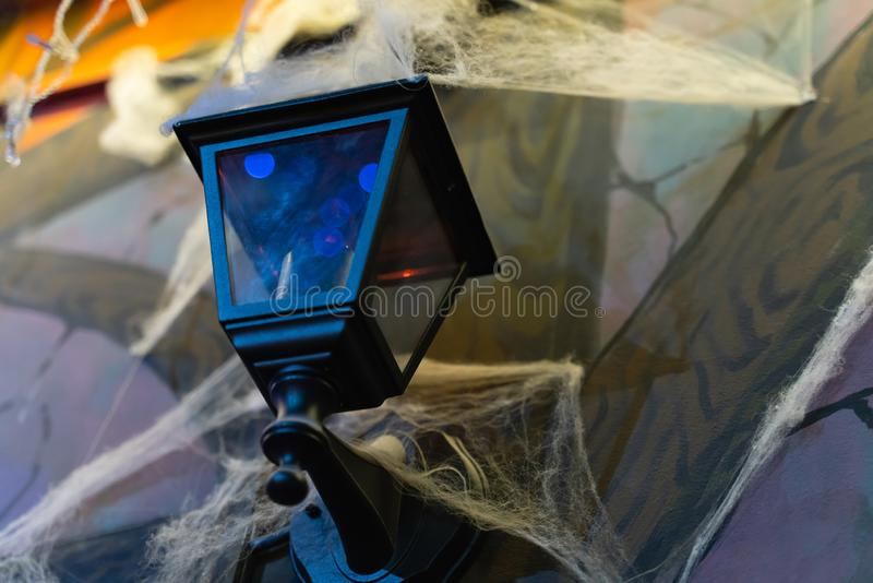 Black lantern in retro style shrouded in cobwebs on the wall. As a background royalty free stock image
