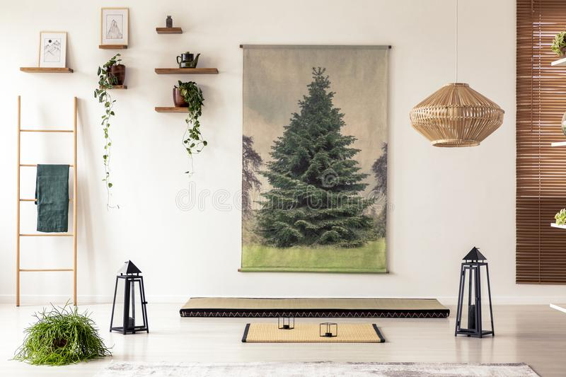 Black lanterns, wooden ladder, tatami mat and tree graphic in mi. Nimal interior with asian design. Real photo stock images