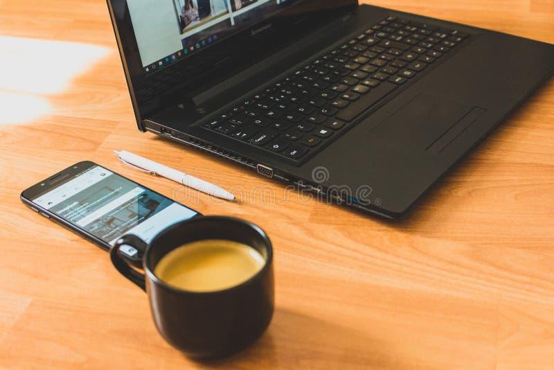 Black Laptop Computer and Black Ceramic Tea Cup stock images