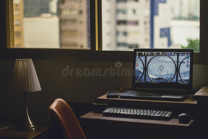 Black Laptop Computer Turned on Near Window at Daytime royalty free stock images