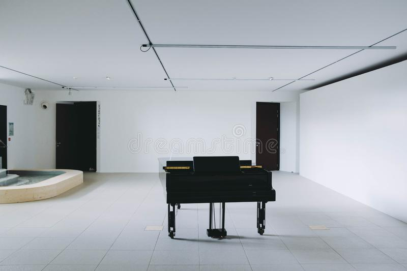 Black large piano in a white room stock images