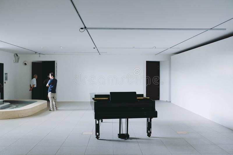 Black large piano in a white room with people around stock image