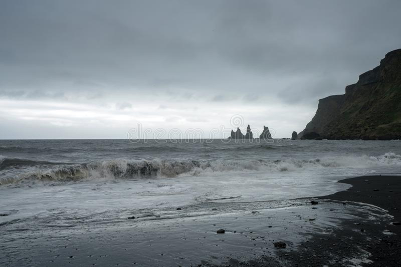 The black lava beach in the city of Vik overlooking the sea. And the basalt stacks on reynisfjara royalty free stock photos