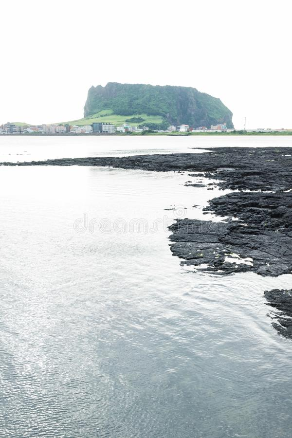 Black lava formation from lake view to Ilchulbong volcano crater, Seongsan, Jeju Island, South Korea, vertical royalty free stock photo