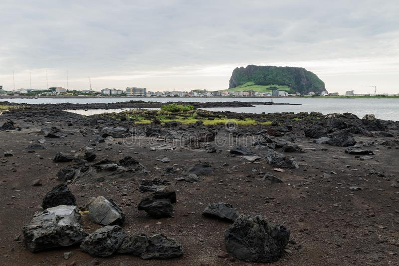 Black lava stones and beach with lake view to Ilchulbong volcano crater, Seongsan, Jeju Island, South Korea royalty free stock images