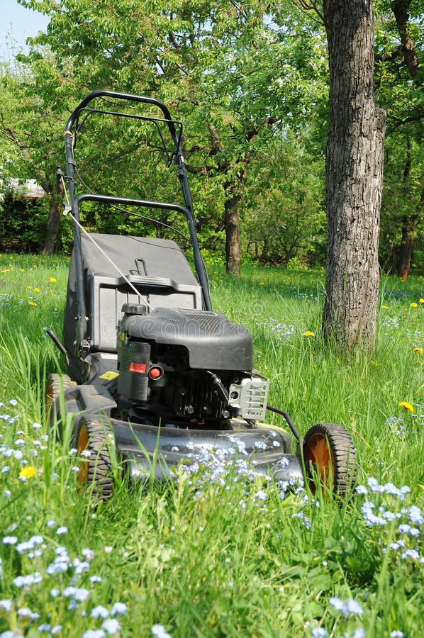 Black lawn mower. With a combustion engine in a garden stock photos