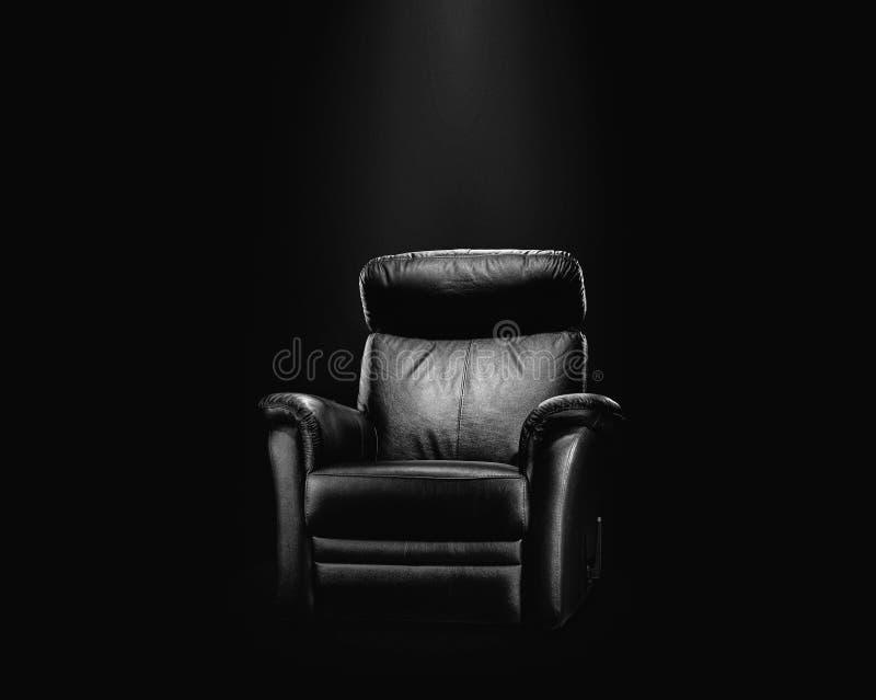 Black leather armchair in spotlight royalty free stock photos