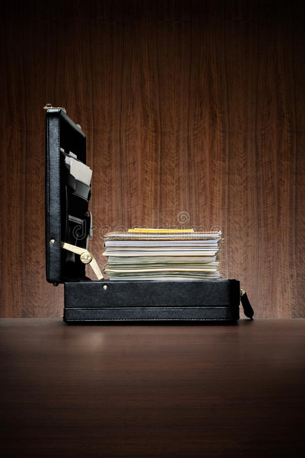 Black leather briefcase with ambitiousl stack of files stock images