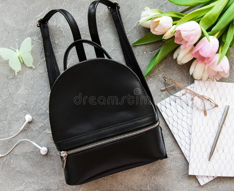 Black leather backpack. And flowers on a grey concrete background stock photography