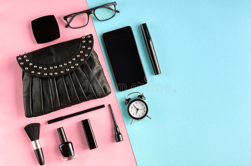 Black leather bag with nail polish, pomade, mascara, alarm clock and eye shadows on pink and blue background composition. Flat lay and top view photo, brush royalty free stock photography