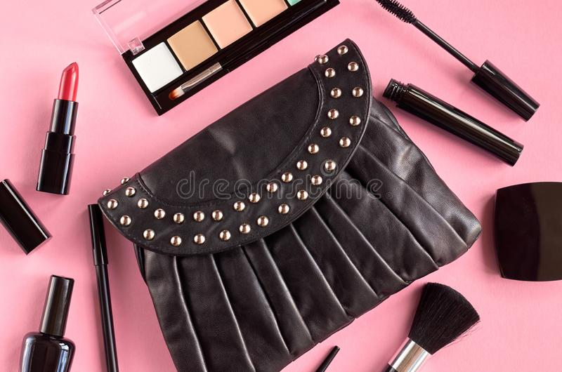 Black leather bag with nail polish, pomade, mascara and eye shadows on pink background composition. Flat lay and top view photo, brush, nail-varnish, blush royalty free stock images