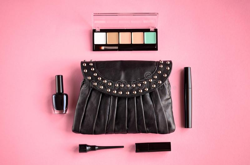Black leather bag with nail polish, pomade, mascara and eye shadows on pink background composition. Flat lay and top view photo, nail-varnish, blush, make-up stock image