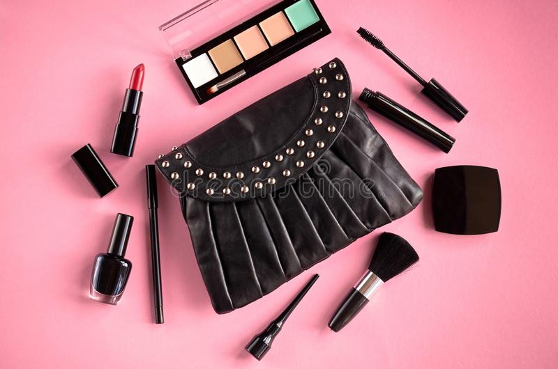 Black leather bag with nail polish, pomade, mascara and eye shadows on pink background composition. Flat lay and top view photo, brush, nail-varnish, blush royalty free stock photo