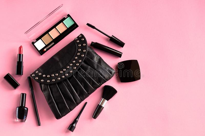 Black leather bag with nail polish, pomade, mascara and eye shadows on pink background composition. Flat lay and top view photo, brush, nail-varnish, blush royalty free stock image