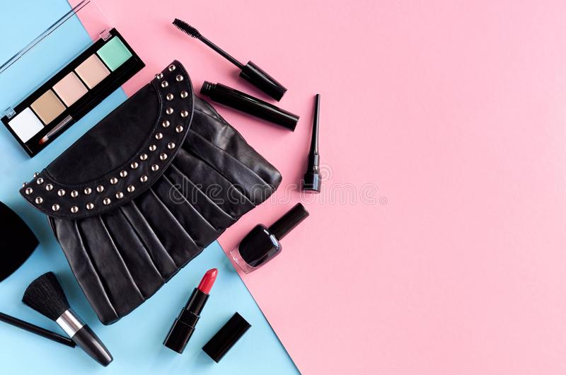 Black leather bag with nail polish, pomade, mascara and eye shadows on pink and blue background composition. Flat lay and top view photo, brush, nail-varnish stock photography