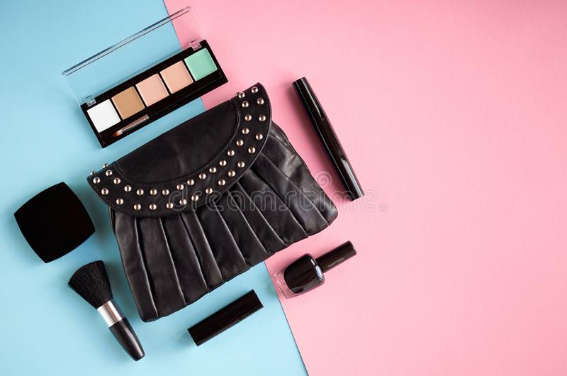 Black leather bag with nail polish, pomade, mascara and eye shadows on pink and blue background composition. Flat lay and top view photo, brush, nail-varnish royalty free stock image
