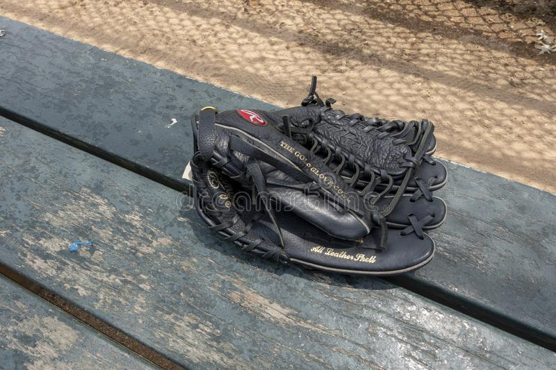 Black leather baseball glove on the bench batters fence casting royalty free stock images
