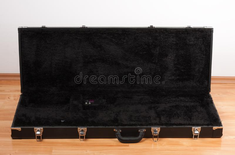 Black leather case for electric guitar on the floor in living room stock photography