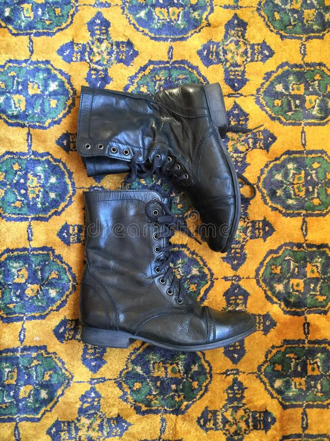 Black Leather Combat Boots on Oriental Rug. These fashionable black combat boots lie on an old yellow patterned oriental rug on the floor royalty free stock photography