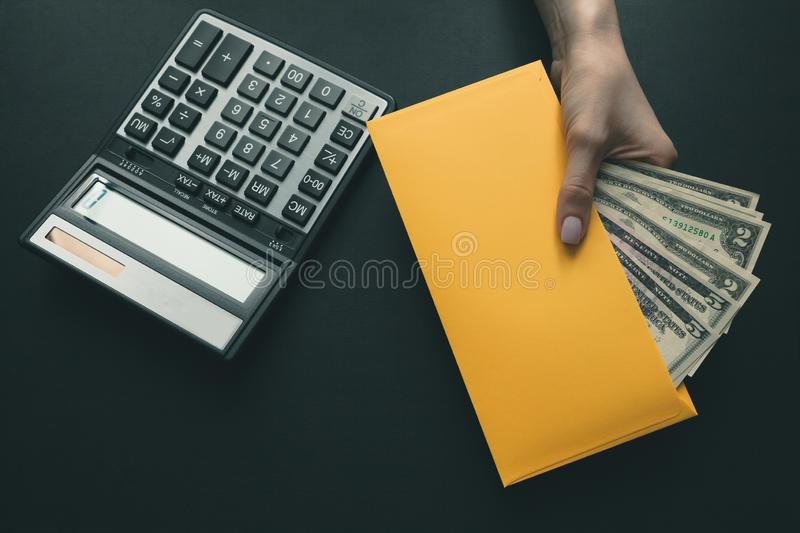 On the black leather desk a calculator, the girl holds in her hand a yellow envelope with money, salary for work stock photos