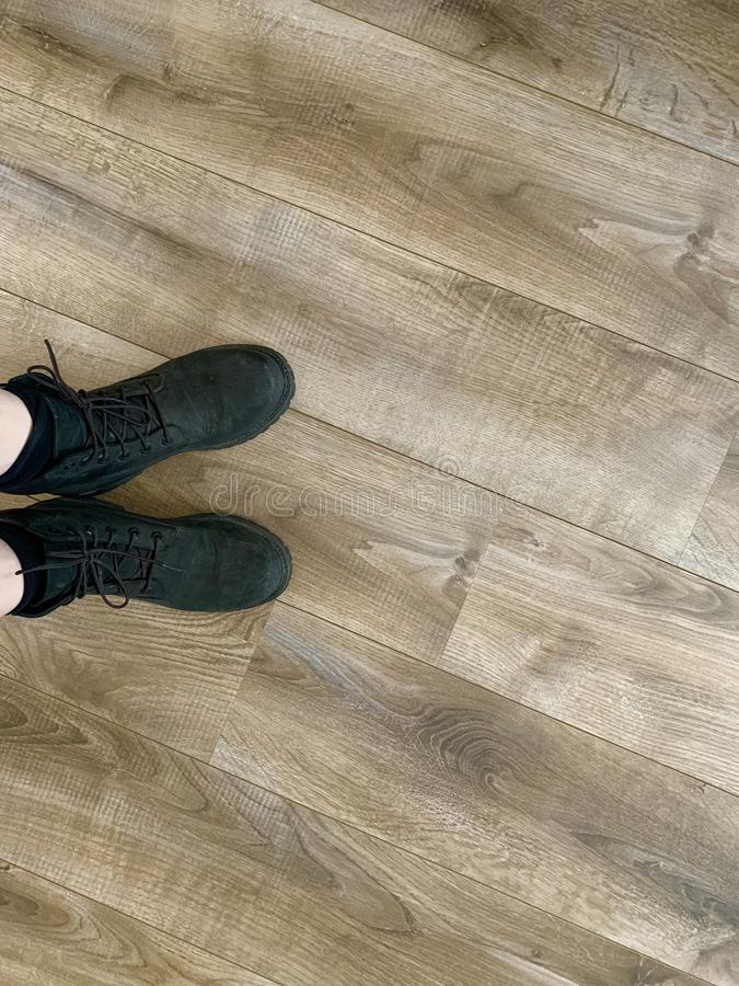 Black leather hiking boots on a wooden floor. Black leather hiking boots with laces  on a wooden floor stock photography