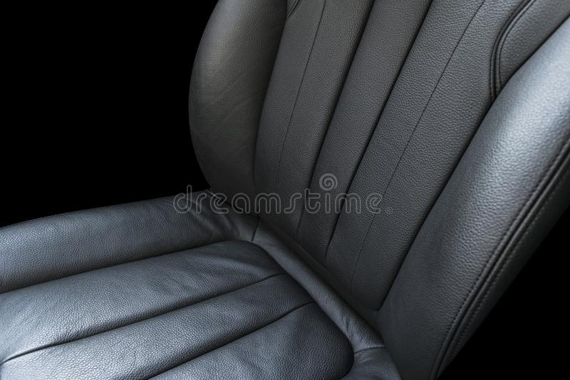 Black leather interior of the luxury modern car. Perforated Leather comfortable seats isolated on black background. Modern car int. Erior details. Car detailing royalty free stock photo