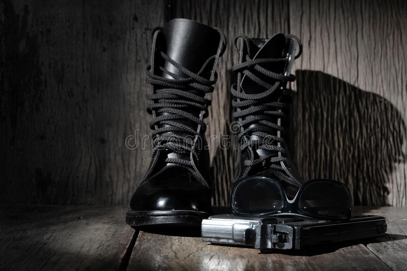 Black leather military combat boots. With a gun and black sunglasses on wood background stock photo