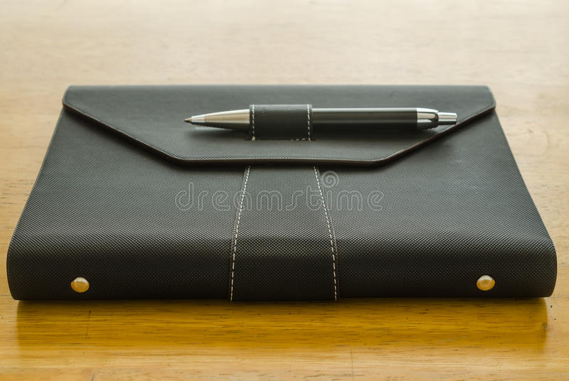 black leather organizer with pen stock photos