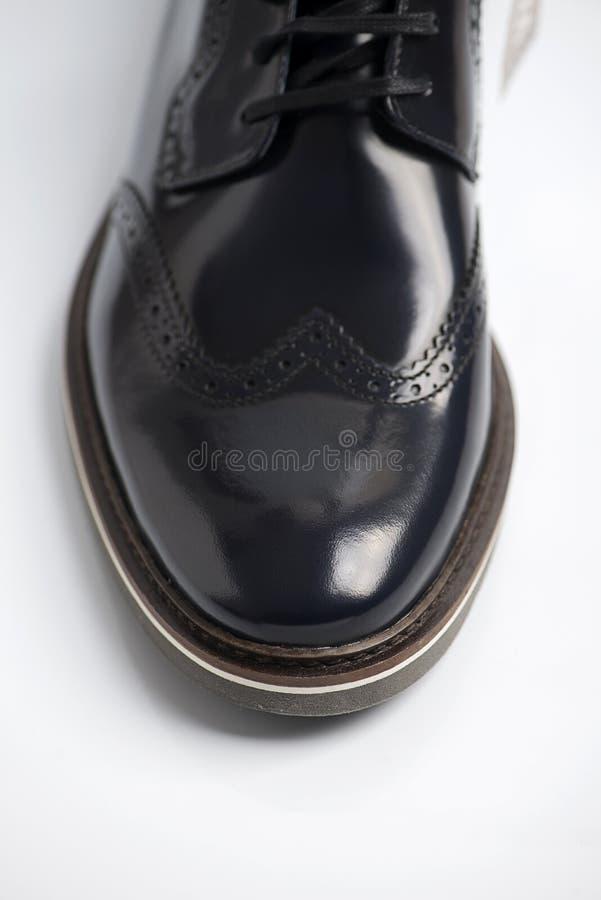 Black leather shiny boot. Vertical studio shot.  stock photography
